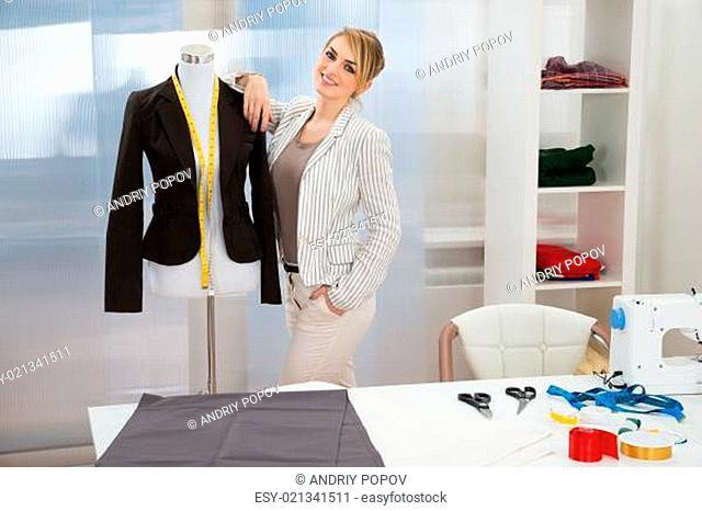 Portrait Of Smiling Fashion Designer With Dressmakers Model