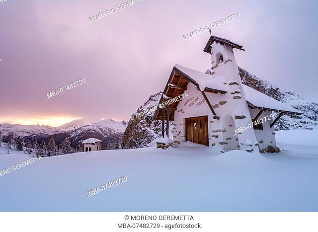 Small white chapel in winter on top of Falzarego pass in the Dolomites, Cortina d'Ampezzo, Belluno, Veneto, Italy