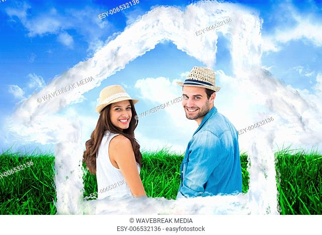 Composite image of happy hipster couple holding hands and smiling at camera