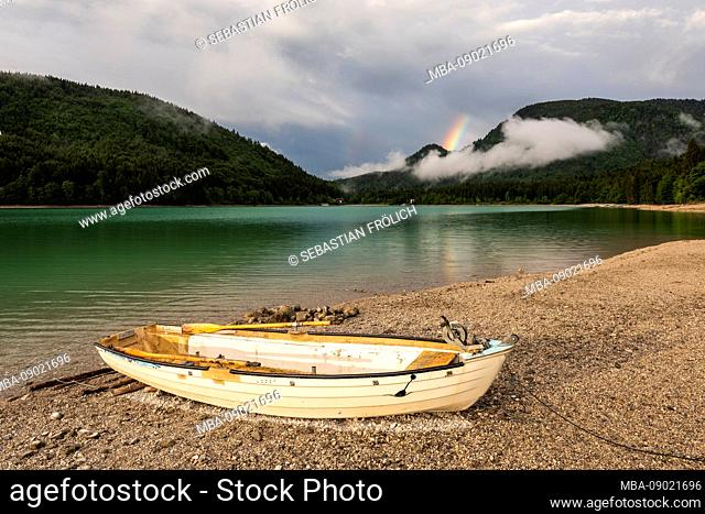 Lonely fishing boat on the shore of lake Walchensee, in the background a rainbow over the rhombus