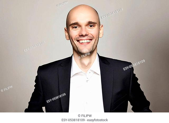 Studio shot of young man looking at the camera. Horizontal format, he is smiling, he is wearing a black jacket