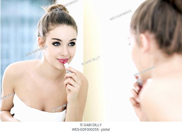 Portrait of teenage girl putting lipstick on while looking at her mirror image