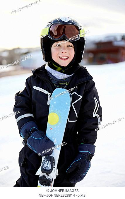 Smiling boy with skis