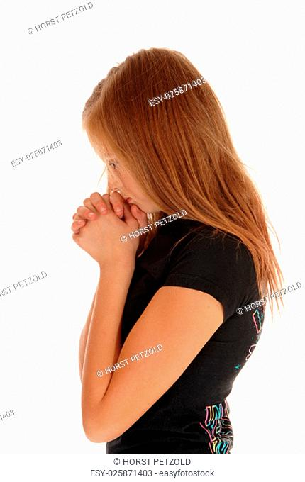 A pretty girl in a black sweater wit her hands folded and praying, standing.isolated for white background.