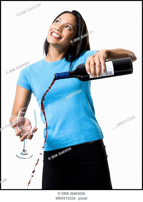 Distracted woman pouring red wine and missing glass