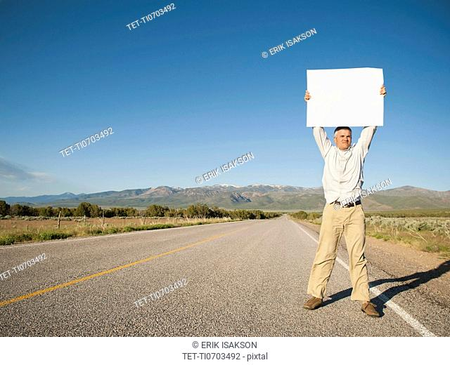 Mid-adult man hitch-hiking in barren scenery