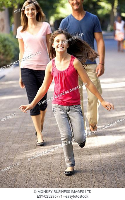 Daughter Runs Ahead Of Parents On Walk Through Summer Park