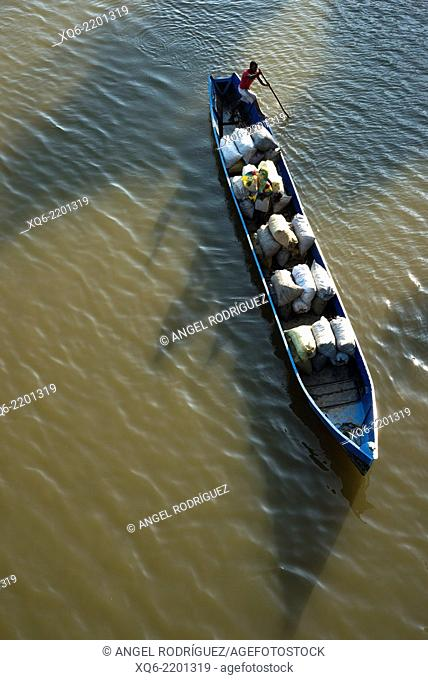 Man pulling his wooden boat in Madagascar. River transport it's still a fast transport system in some far away regions