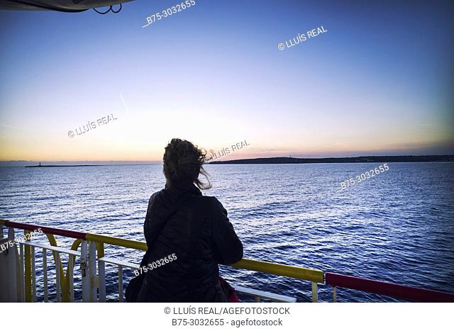 Silhouette of unrecognizable woman on the deck of a ferry boat in port. Mediterranean Coast, Mahon, Menorca, Balearic Islands, Spain