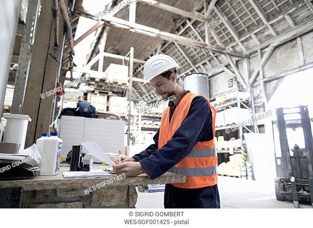 Warehouseman in storehouse signing an order