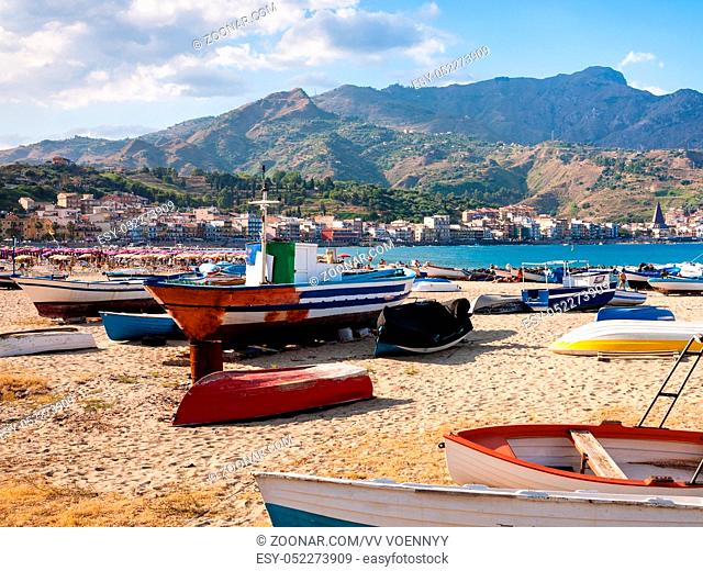 travel to Italy - urban beach with boats in Giardini Naxos town in Sicily in summer evening