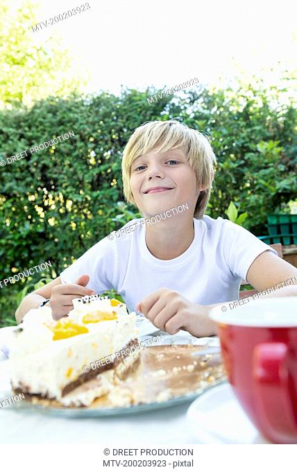 Smiling young boy with cream cake