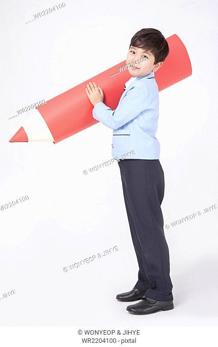 Elementary school boy in school uniforms standing sideways and holding a big red pencil staring forward