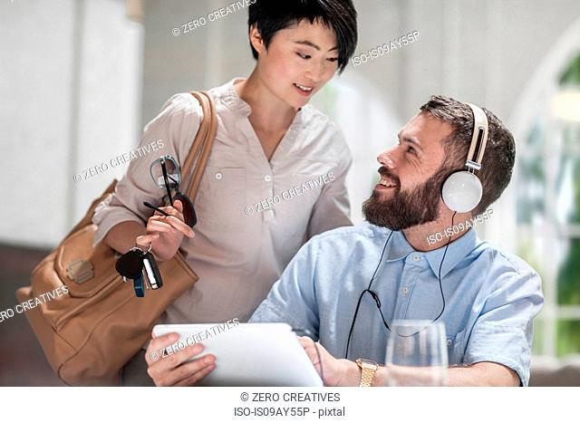 Woman speaking with man using digital tablet with headphones
