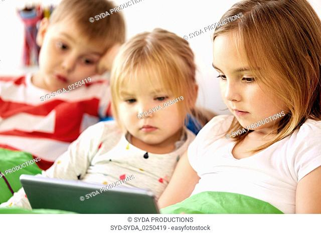 little kids with tablet pc in bed at home