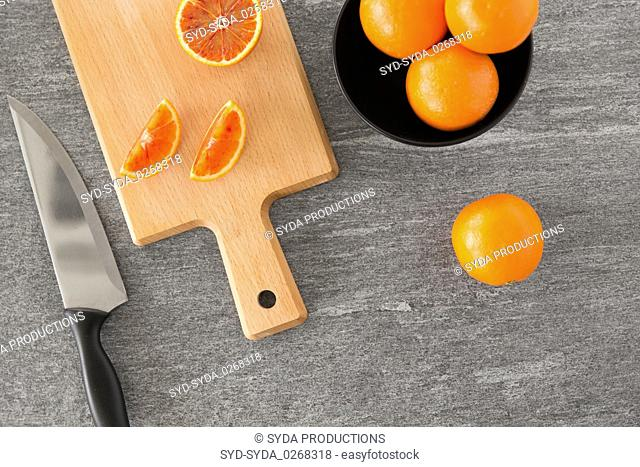 close up of oranges and knife on cutting board