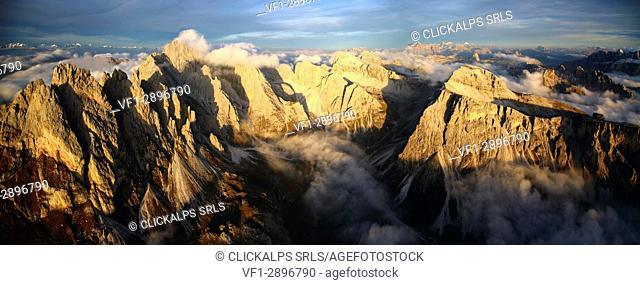 Aerial view of the mountain range of Odle surrounded by clouds. Dolomites Val Funes Trentino Alto Adige South Tyrol Italy Europe