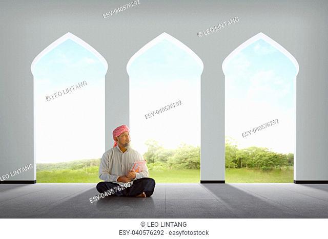 Elderly asian muslim man holding Koran in the mosque