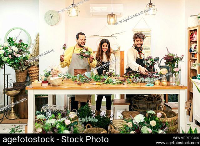 Florists arranging flowers and plant at flower shop