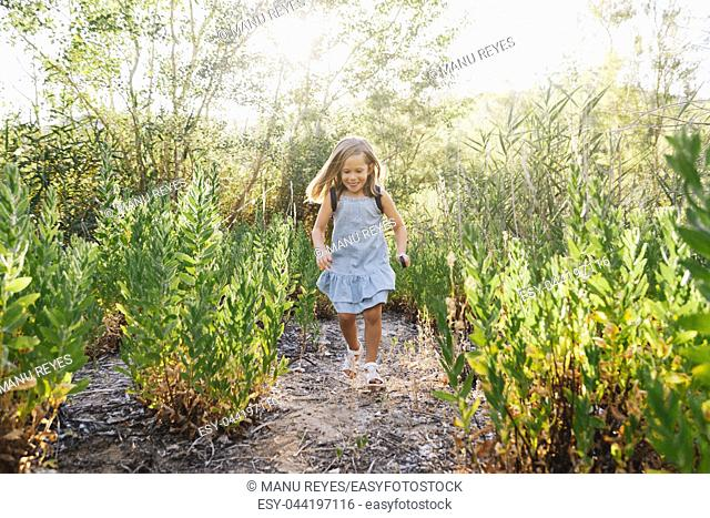 Young blonde girl running in the field wearing a dress with a magnifying glass in her hand an backpack