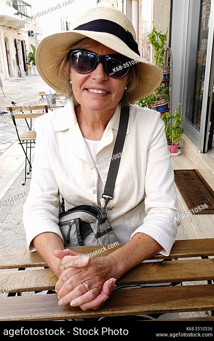 Woman, 69, at a cafe in Polignano a Mare, Puglia, Italy