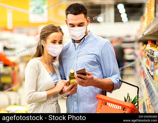 couple in masks with phone and olive oil at store