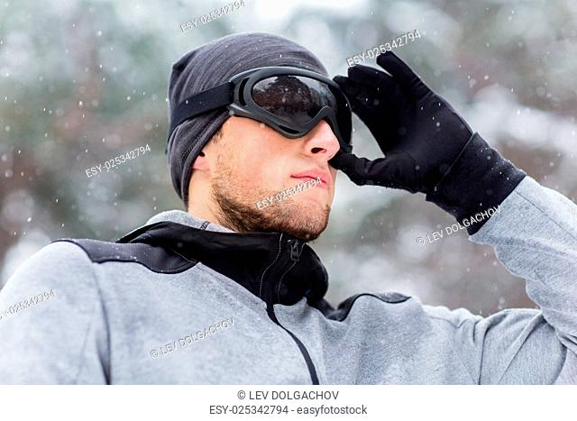 fitness, winter sport, people and healthy lifestyle concept - close up of young man in ski goggles outdoors
