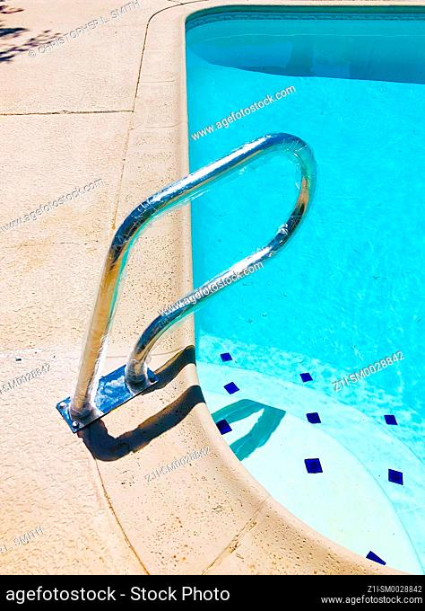 Handrail affixed to the edge of a swimming pool near the steps into the shallow end