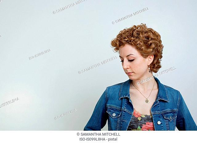 Young woman looking down, studio shot