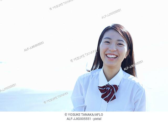 Young Japanese woman in a high school uniform by the sea, Chiba, Japan