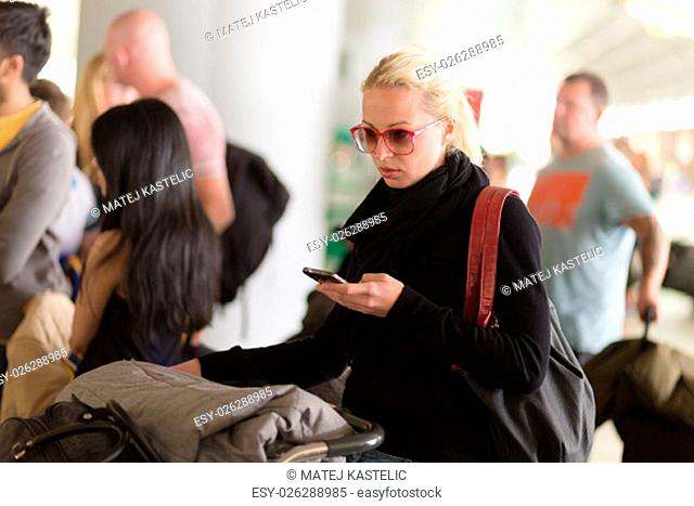 Casual blond young woman using her cell phone while queuing for flight check-in and baggage drop. Wireless network hotspot enabling people to access internet...