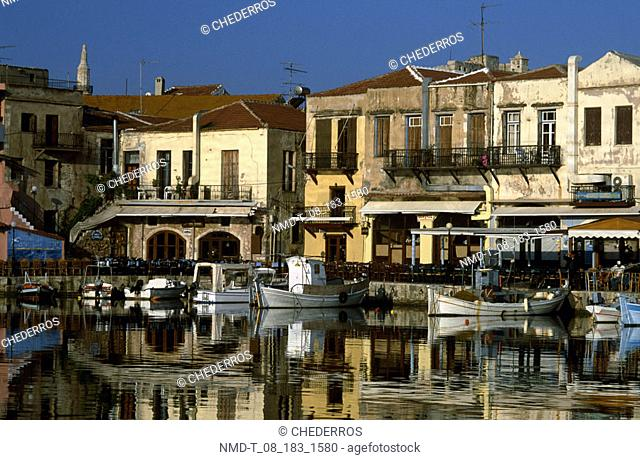 Reflection of buildings and boats in water, Crete, Greece