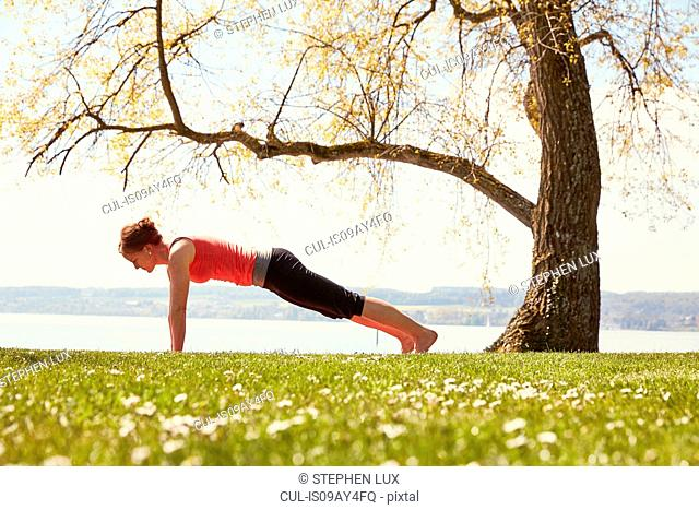 Side view of woman doing yoga push up