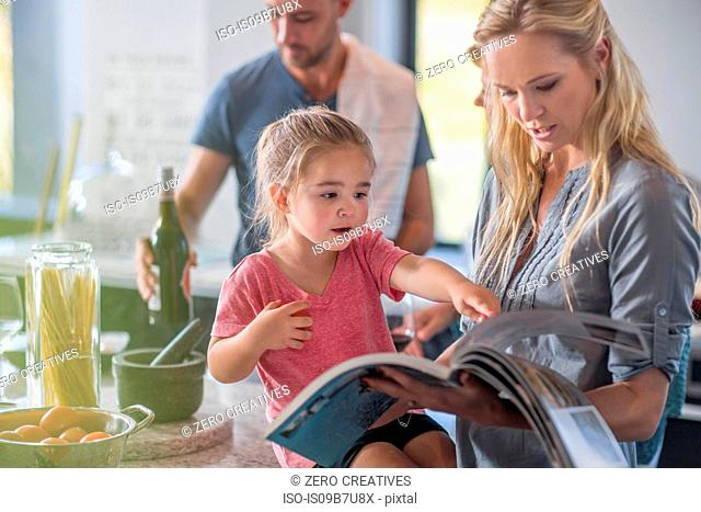 Family in kitchen, mother and daughter looking through book