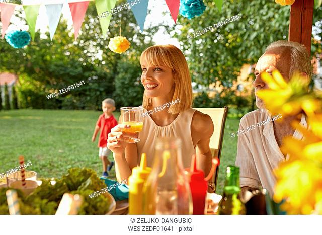 Smiling woman drinking orange juice on a garden party