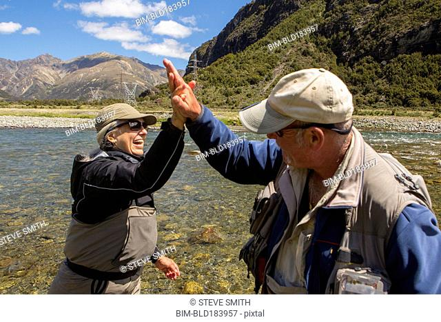 Caucasian couple high-fiving in remote river
