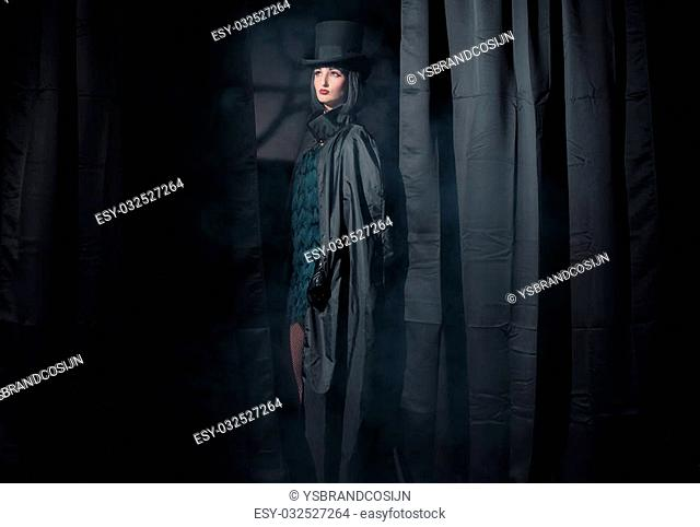 Witch fashion woman wearing black cape and hat. Standing between curtains