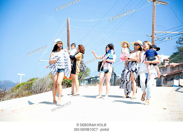 Four adult female friends and their babies strolling along beach, Malibu, California, USA