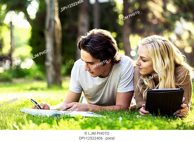 A young couple lays down studying outdoors on the grass on the university campus with a textbook and tablet and checking social media on a smart phone; Edmonton