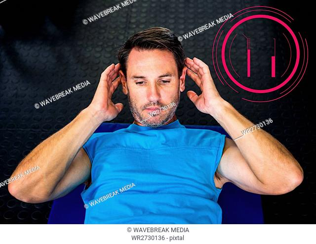Fit man performing crunches exercise in gym against fitness interface in background