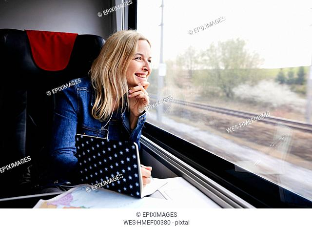 Laughing blond woman with notebook travelling by train looking out of window