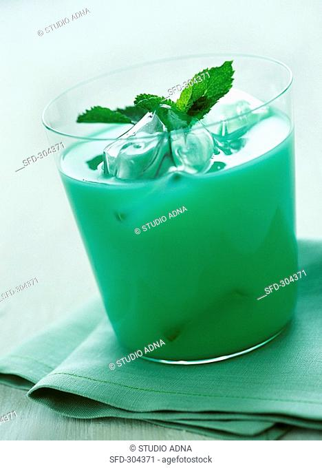 Green cocktail with ice cubes and mint leaves