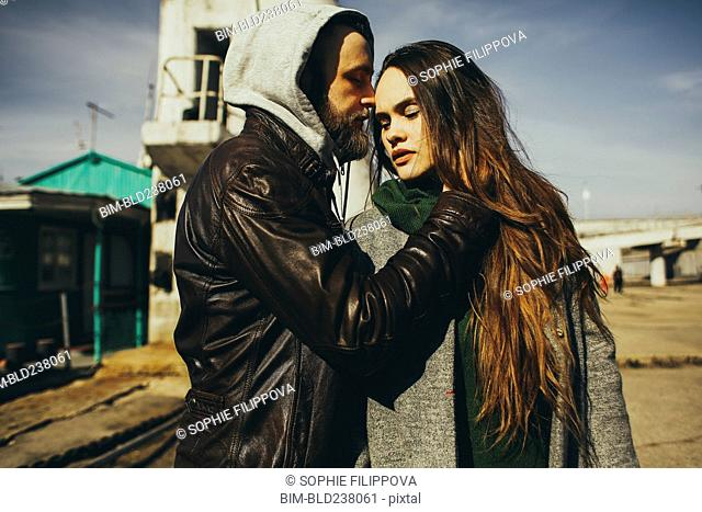 Caucasian man hugging woman outdoors