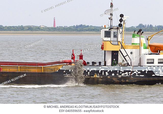 Sand dredging boat drawing away from coast shoreline to pump sand - Waddensea