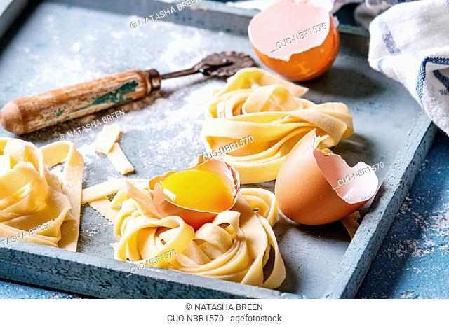 Fresh raw uncooked homemade twisted pasta tagliatelle with egg yolk, shell and pasta cutter in wooden tray with kitchen towel over light blue concrete...