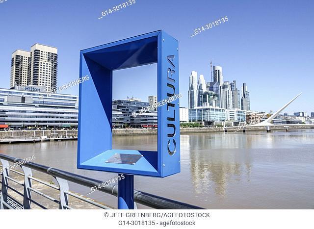 Argentina, Buenos Aires, Puerto Madero, Rio Dique, water, riverfront, city skyline, promenade, Puente De La Mujer, pedestrian suspension swing bridge designed...