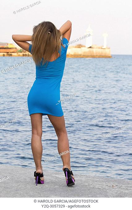 Beautiful, attractive Ukrainian woman wearing a blue dress posing near the black sea for a photographic sequence in Yalta, Crimea