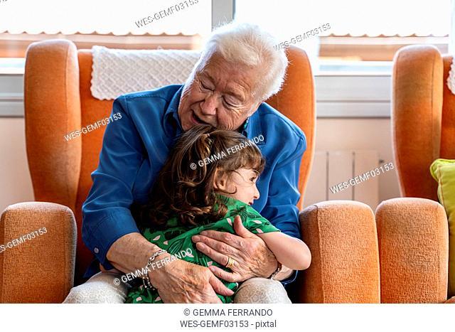Grandmother hugging her granddaughter in living room