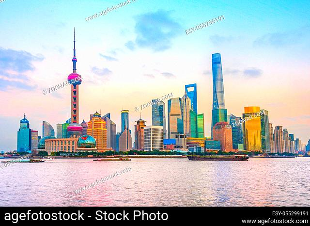 Shanghai metropolis skyline with modern architecture on river bank with scenic sunset sky on background, China