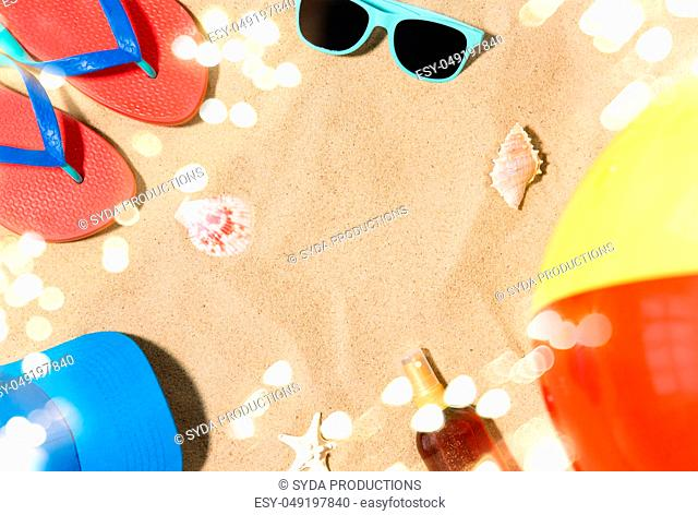 cap, flip flops and shades and beach ball on sand